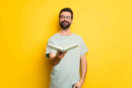 Man with beard and green shirt holding a book and giving it to someone