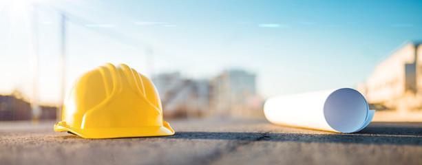 Progetto ingegneria civile in un cantiere. Caschetto di protezione da architetto giallo e foglio con disegno arrotolato poggiato sull'asfalto a terra.