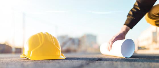 Caschetto giallo e progetto ingegneristico su foglio arrotolato poggiati su una strada asfaltata con mano di ingegnere.