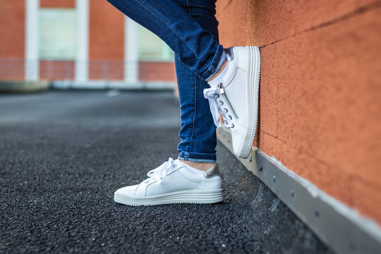 Woman with leather white sneaker leaning wall in city, close-up side view