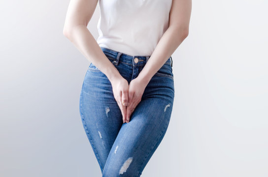 Young woman in jeans standing with her hands between legs