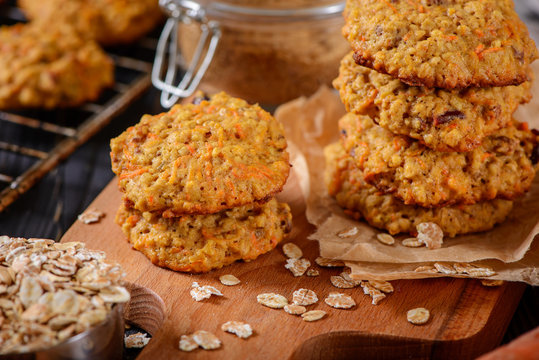 Carrot oatmeal cookies with with cranberries and cinnamon on the rustic background