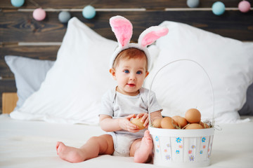 Portrait of adorable baby with bunny ears and easter basket