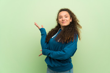 Teenager girl over green wall extending hands to the side for inviting to come