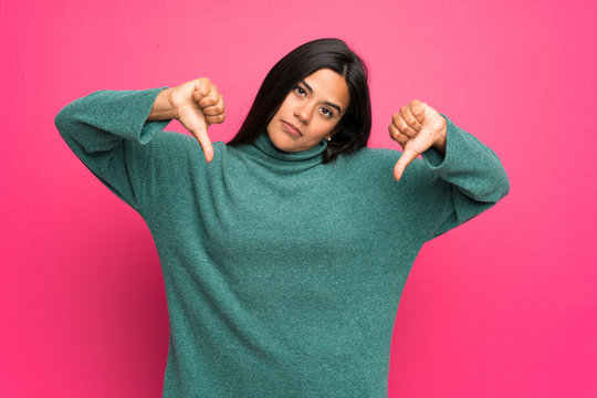 Young Colombian girl with green sweater showing thumb down