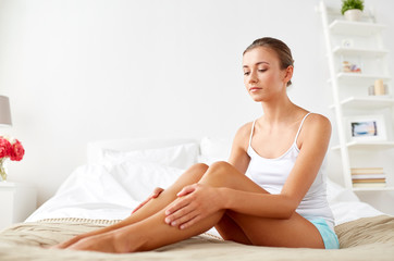 people, beauty and bodycare concept - beautiful woman with bare legs sitting on bed at home bedroom