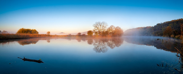 Wall Murals Deep brown Calm Lake in Autumn at Sunrise, Fog rising from the water, blue sky
