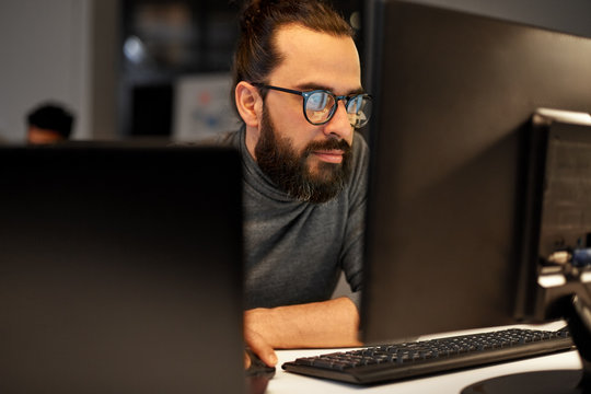 deadline, technology and people concept - close up of creative man in glasses working at night office and thinking