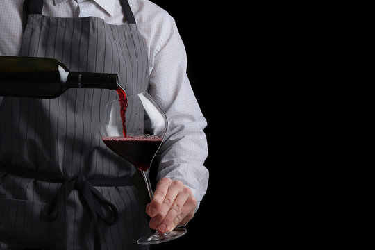 the waiter pours wine in glass on dark background