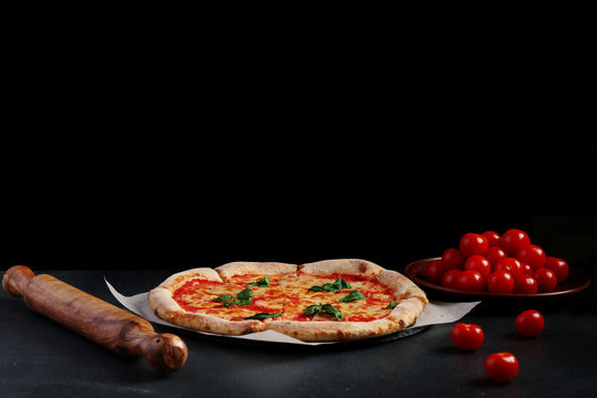 izza margarita with tomatoes and ingredients on dark stone background with copy space