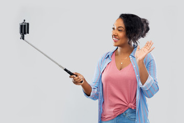 technology and people concept - happy african american woman taking picture by smartphone on selfie stick and waving hand over grey background