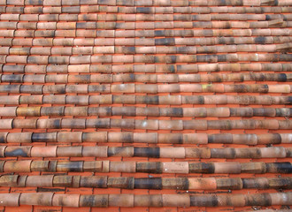 full frame image of an oldclay pantile roof with curves orange tiles in long rows
