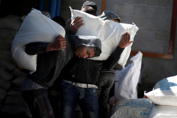 Palestinians carry sacks of flour inside a United Nations food distribution center in Al-Shati refugee camp in Gaza City