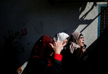 Palestinians wait to receive aid at a United Nations food distribution center in Al-Shati refugee camp in Gaza City