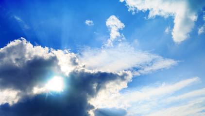 Blue sky with big clouds and sunlight.