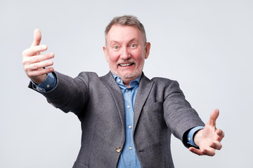 Senior man in suit joyfully stretches hands forward on a white background.
