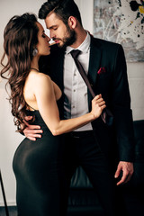 attractive woman in black dress holding tie of passionate man standing in suit