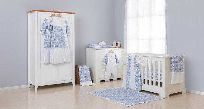 Shot of a crib in a modern white nursery room