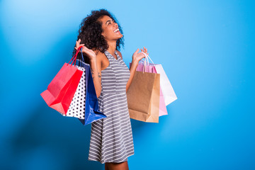 Young black woman holding shopping bags on blue backgrond.