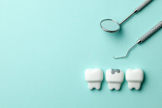 Healthy white teeth and tooth with caries on green mint background  and dentist tools mirror, hook. Copy space for text.