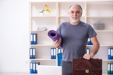 White bearded old man employee doing exercises in the office