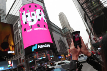 A woman takes a photo signage for Lyft as it is displayed at the NASDAQ MarketSite in Times Square in celebration of its initial public offering (IPO) on the NASDAQ Stock Market in New York