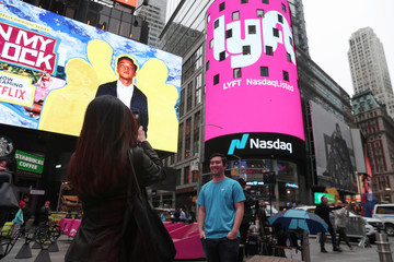 Brian Friedenberg, an intern for Lyft, has his picture taken in front of signage for Lyft as it is displayed at the NASDAQ MarketSite in Times Square in celebration of its initial public offering (IPO) on the NASDAQ Stock Market in New York