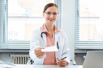 Arzt halt ein Rezept für ein Medikament in die Kamera