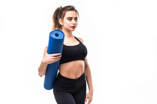 Young attractive woman holding a yoga mat isolated on white background