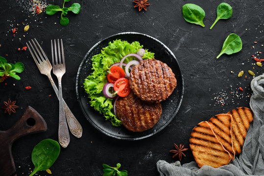 fried cutlet for burger with vegetables. In a black plate on a wooden background Top view. Free space for your text. Flat lay