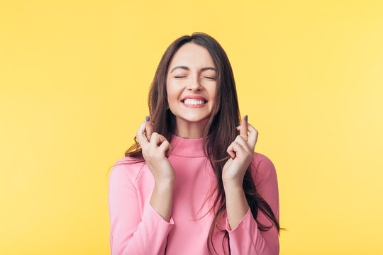 Young beautiful woman crossing her fingers and wishing for good luck over yellow background