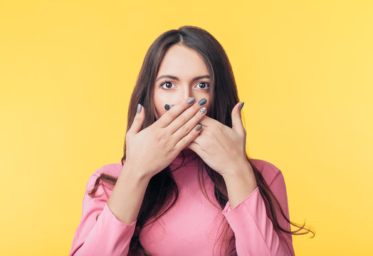 Surprised excited woman covering her mouth with hands on yellow background