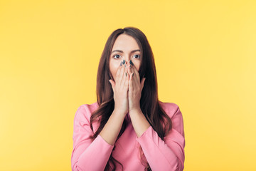 Shocked excited woman covering her mouth with hands on yellow background