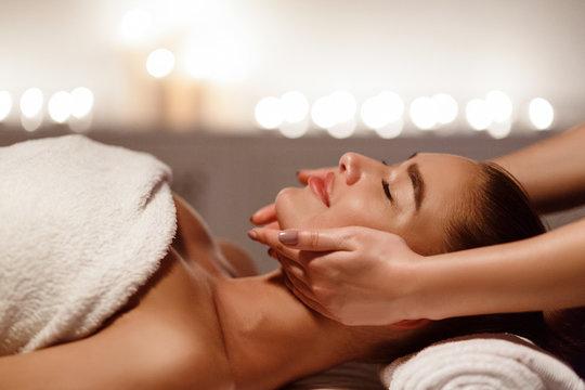 Woman enjoying anti aging facial massage, side view