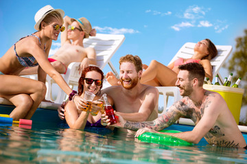 Cheerful men and women toasting with drink in swimming pool