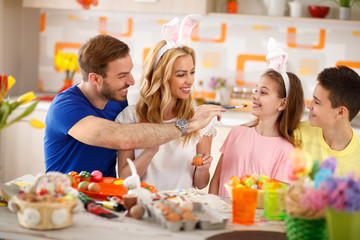 Family having fun while painting Easter eggs
