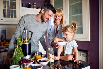 Family with daughter eating in kitchen