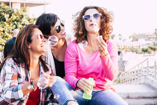 Playful real life concept with three cheerful smiling middle age women friends anejoying and laughing togehter playing with soap bubbles in outdoor leisure activity - playful and happiness concept