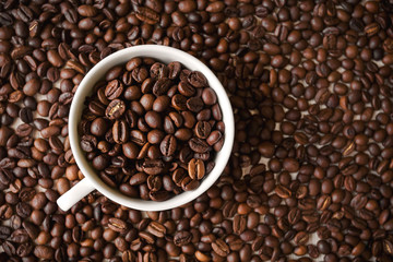 white cup with roasted coffee beans stands on the background of a large number of coffee beans