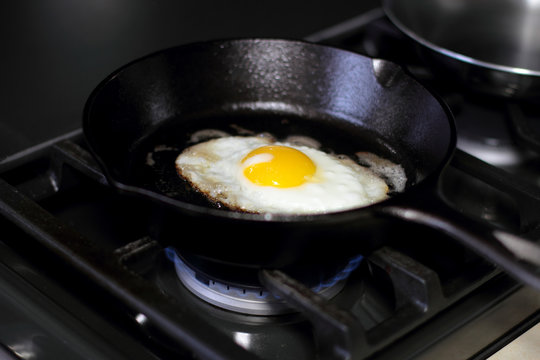 Egg sunny side up frying in a pan on the stove.