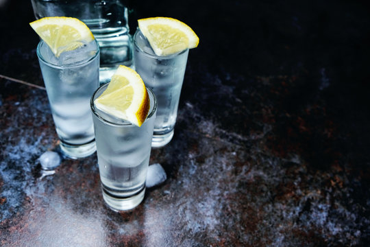 Vodka. Shots, glasses with vodka with ice .Dark stone background.Copy space .Selective focus