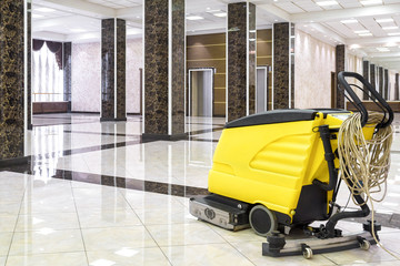 Cleaning machine in the empty office lobby. Yellow vacuum equipment for cleaning is on the shiny marble floor. Concept of professional cleaning and care service. Wall mural