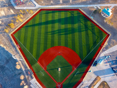Aerial drone wide angle view of a green baseball field diamond in the morning sunlight ready for play.