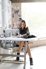 Young designer using sewing machine in an atelier