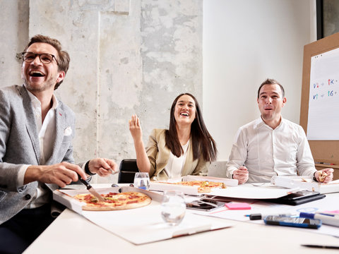 Laughing colleagues having lunch break with pizza in conference room