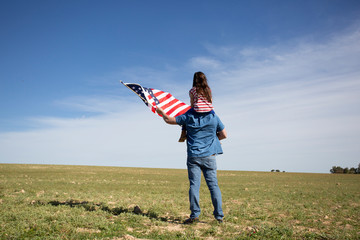 Man with daughter and American flag standing on field in remote landscape