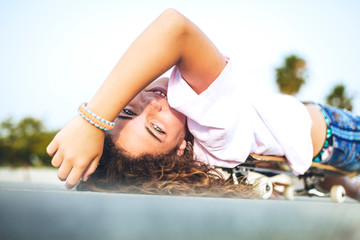 Girl lying on skateboard, looking at camera