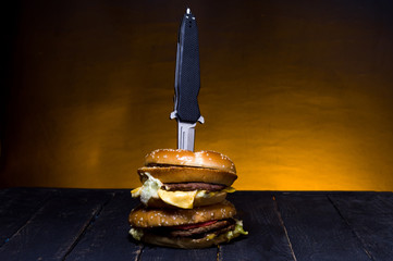 A pocket knife in a burger. Folding knife and burger.