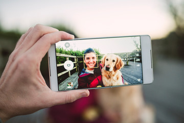 Cell phone picture of a happy young woman with her Golden retriever dog outdoors