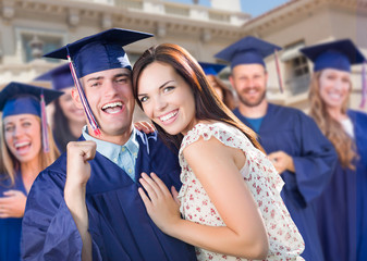 Proud Male Graduate In Cap and Gown with Girl Among Other Graduates Behind